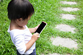 Outdoor portrait of child using a digital tablet or smart phone - asian