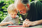 Child using a tablet with his Grandpa