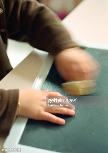 Child using chalkboard and sponge.
