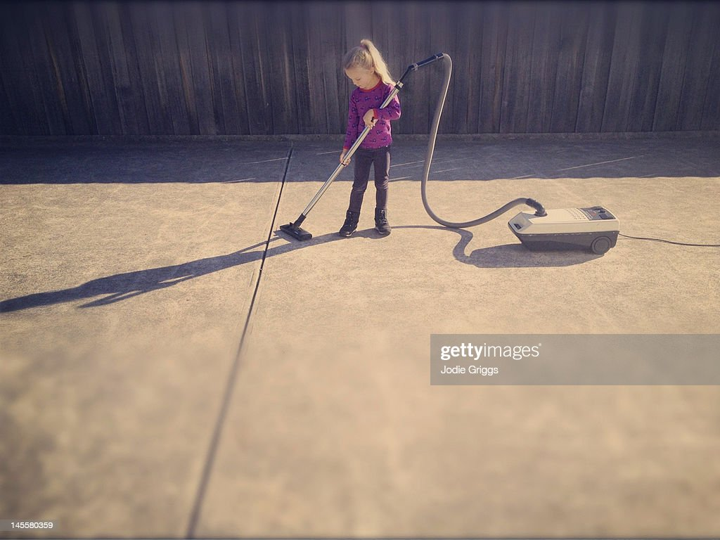 Child using vacuum cleaner outside on concrete : Stockfoto