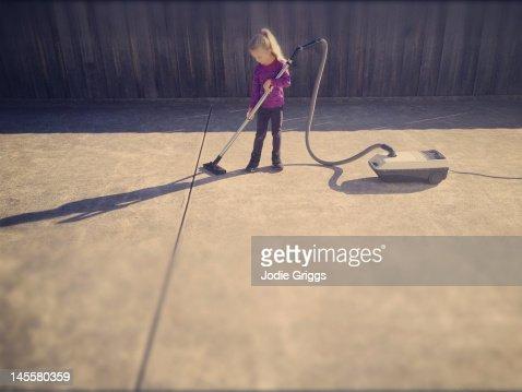Child using vacuum cleaner outside on concrete : Bildbanksbilder