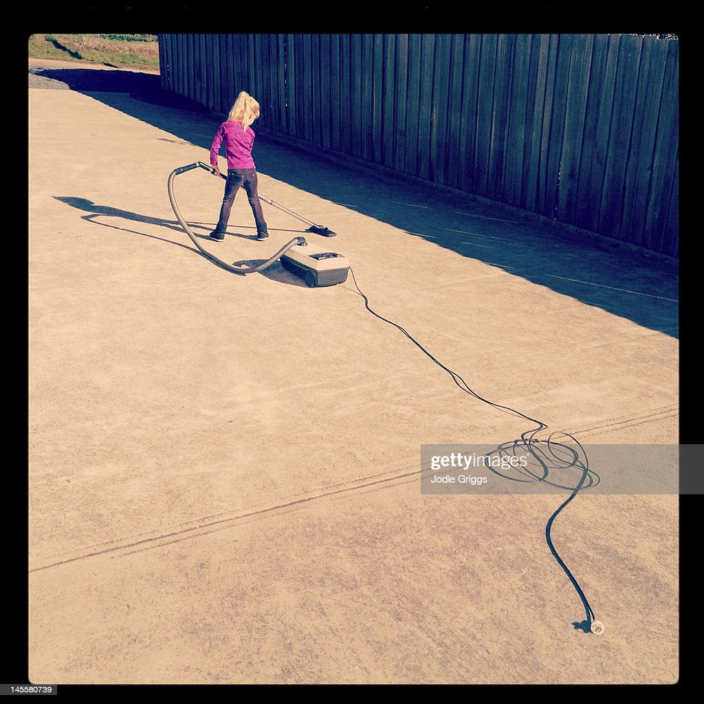 Child using vacuum cleaner outside on concrete : Stock Photo
