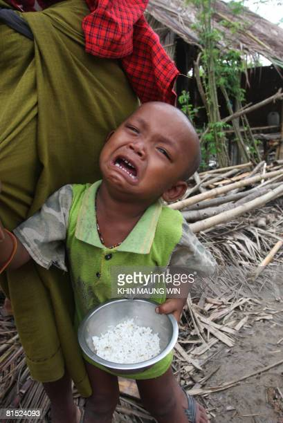 A child victim of Cyclone Nargis is seen clutching a bowl of rice in the town of Dedaye in the Irrawaddy Delta some 250 miles from Yangon on June 9...