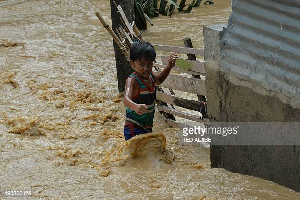 A child wades through floodwaters near his residence at a village in Santa Rosa town Nueva Ecija province north of Manila on October 19 a day after...