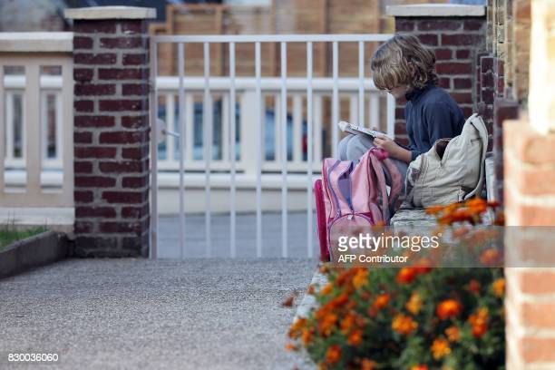 A child waits in front of his closed school on September 10 2014 in Ganzeville in Normandy where the mayor decided to close the school on Wednesday...