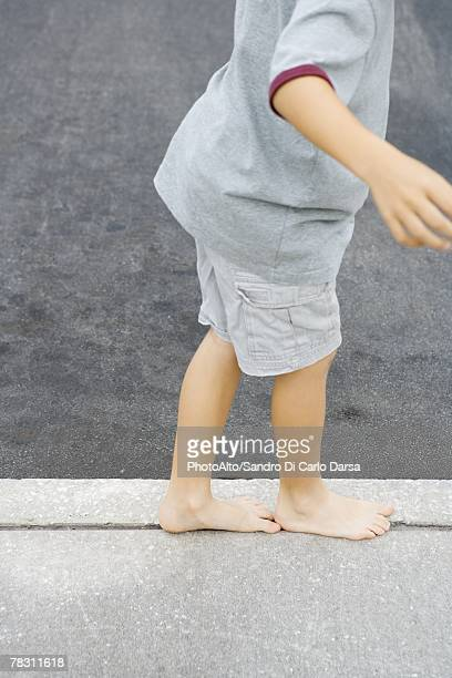 Child walking along crack in sidewalk, cropped view