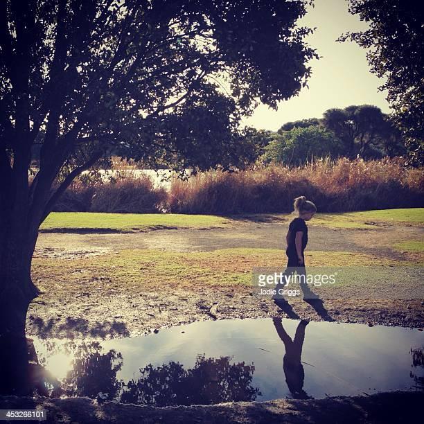 Child walking beside large puddle at park