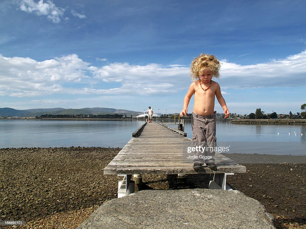 Child walking down old wooden jetty by the river : Stock Photo