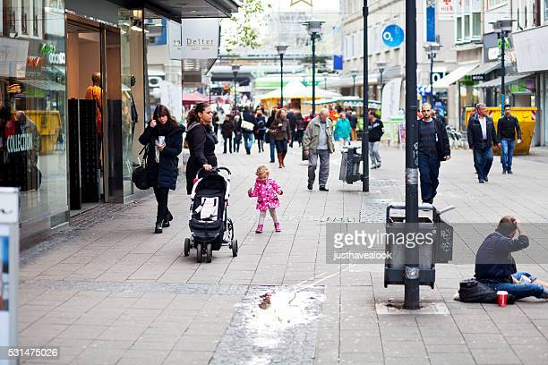 Child walking in pedestrian zone between people