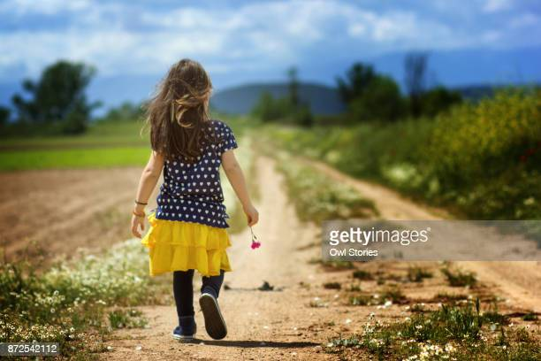 Child walking on a dirt road