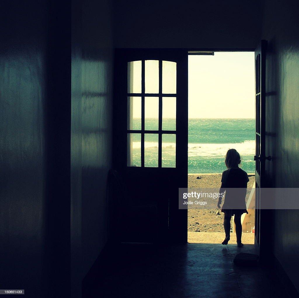 Child walking through open doorway : Stock Photo