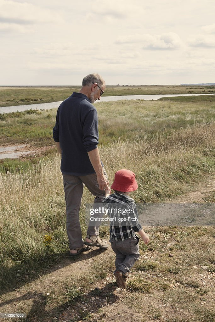 Child walking with grandad : Stock Photo