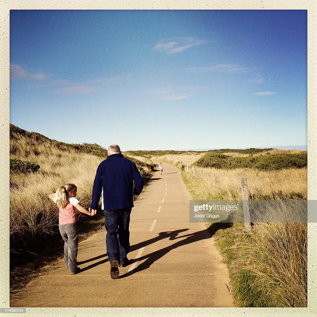 Child walking with grandfather holding hands