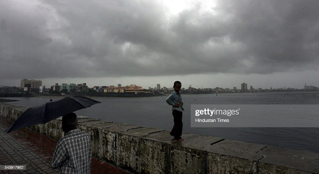 A child walks along the promenade at Bandra reclamation, as dark clouds gather over the city's skyline.