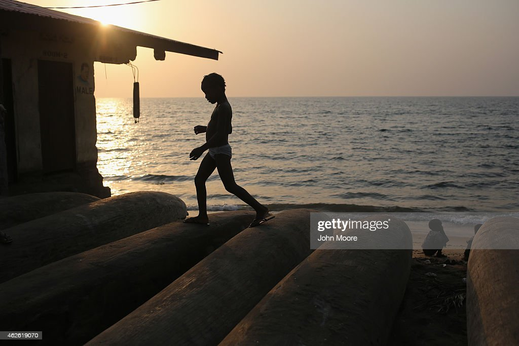 A child walks atop fishing boats in the West Point township on January 31 2015 in Monrovia Liberia Life has slowly begun to return to normal for many...