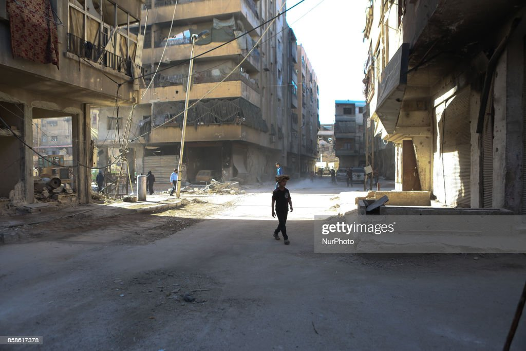 A child walks beside destruction rubble of a building in the rebel. held town of Douma, on the eastern outskirts of Damascus, on October 7. 2017 following reported air strikes by Syrian government forces.