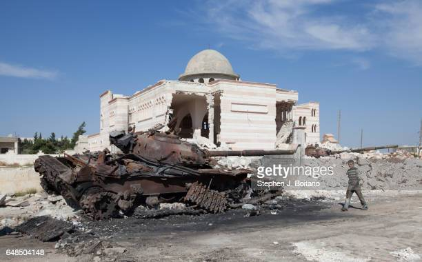 A'ZAZ ALEPPO SYRIA A child walks by a destroyed tank near a damaged mosque in A'zaz Syria