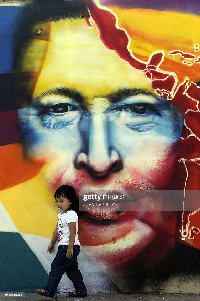 A child walks by a graffitti at the Mountain Barracks (Cuartel de la Montana) where the remains of late Venezuelan President Hugo Chavez are staying in, in the 23 de Enero low income neighborhood in Caracas, on March 28, 2013.