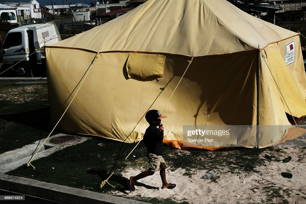 A child walks by a tent on the nearly destroyed island of Barbuda on December 8, 2017 in Cordington, Barbuda. Barbuda, which covers only 62 square miles, was nearly leveled when Hurricane Irma made landfall with 185mph winds on the night of September six. Only two days later, fearing Barbuda would be hit again by Hurricane Jose, the prime minister ordered an evacuation of all 1,800 residents of the island. Most are now still in shelters scattered around Barbuda's much larger sister island Antigua.
