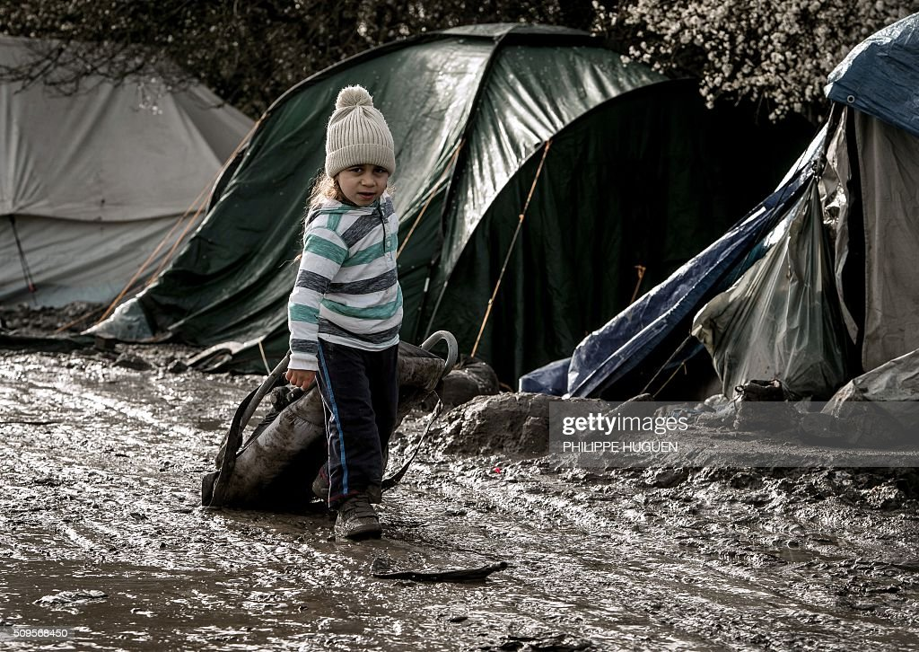 A child walks in the so-called 'Jungle' migrant camp in Gande-Synthe where 2,500 refugees from Kurdistan, Iraq and Syria live on February 11, 2016 in Grande-Synthe near the city of Dunkirk, northern France. / AFP / PHILIPPE HUGUEN