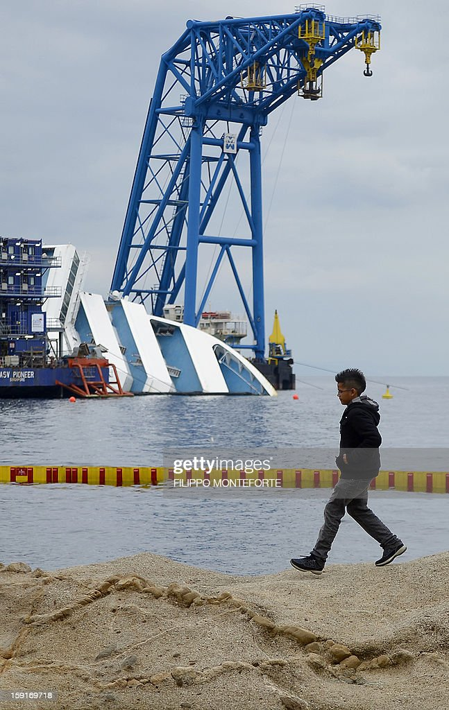 A child walks on the beach as the Costa Concordia cruise ship lays aground on January 9, 2013 on the Italian island of Giglio. A year on from the Costa Concordia tragedy in which 32 people lost their lives, the giant cruise ship still lies keeled over on an Italian island and its captain Francesco Schettino has become a global figure of mockery. AFP PHOTO / FILIPPO MONTEFORTE