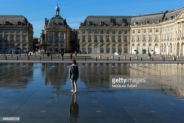 A child walks on the water mirror on the Place de la Bourse in Bordeaux on October 31 2015 as the weather forecast predicts a weekend with higher...