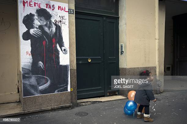 A child walks past a collage picturing a couple kissing inspired by 'Le baiser de l'hotel de ville ' by French photographer Robert Doisneau with an...