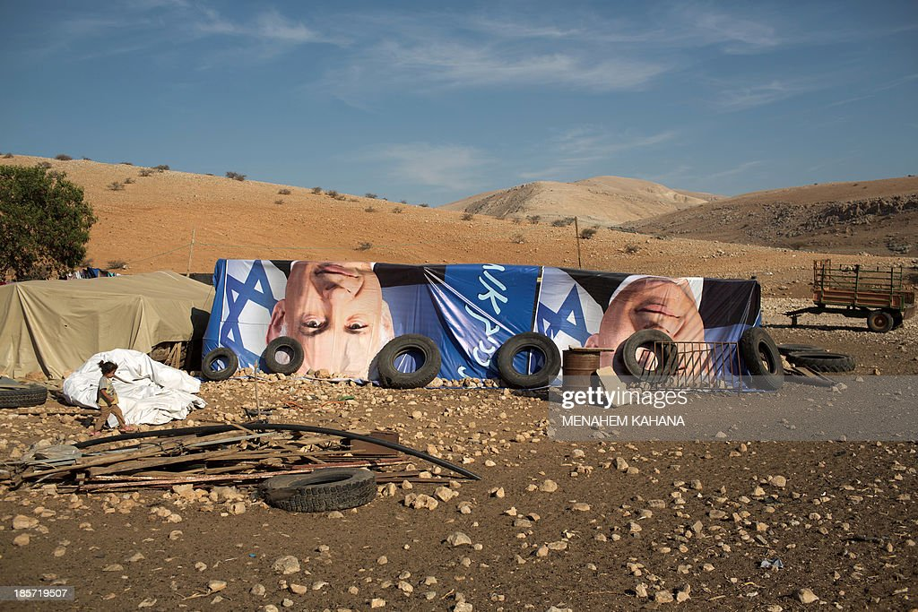 A child walks past makeshifts tents covered with election posters depicting Israeli Prime Minister Benjamin Netanyahu on October 24, 2013 at a West Bank Palestinian Bedouin camp in the Jordan valley. KAHANA