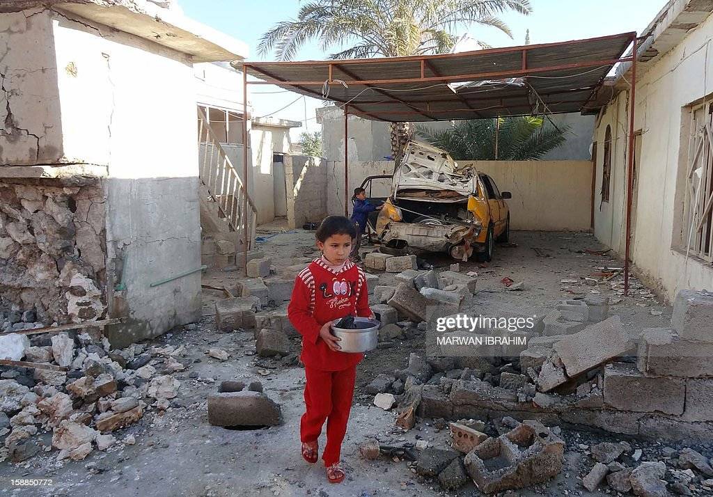A child walks past rubble following an explosion near homes in the ethnically mixed northern city of Kirkuk on January 1, 2013. Seven people were killed and some 18 others injured in several explosions around the city.