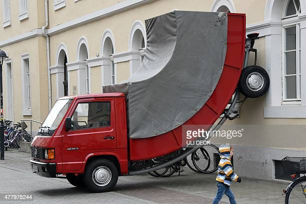 A child walks past the work 'Truck' by Austrian artist Erwin Wurm on June 21 2015 in Karlsruhe southwestern Germany The work is part of the...