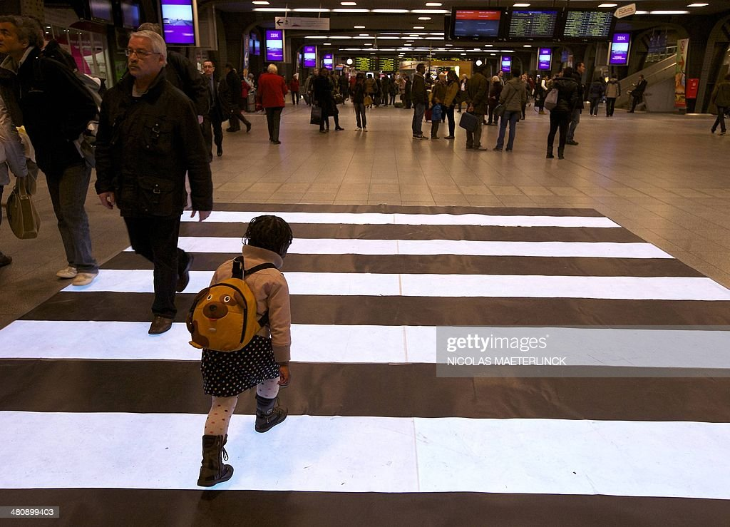 A child walks through a flashing zebra crossing, manufactured by IBM as part of their 'Smarter City Challenge', and being tested in a dedicated zone at Brussels' Midi railway station on March 27, 2014. AFP PHOTO / BELGA PHOTO / NICOLAS MAETERLINCK ** Belgium Out **