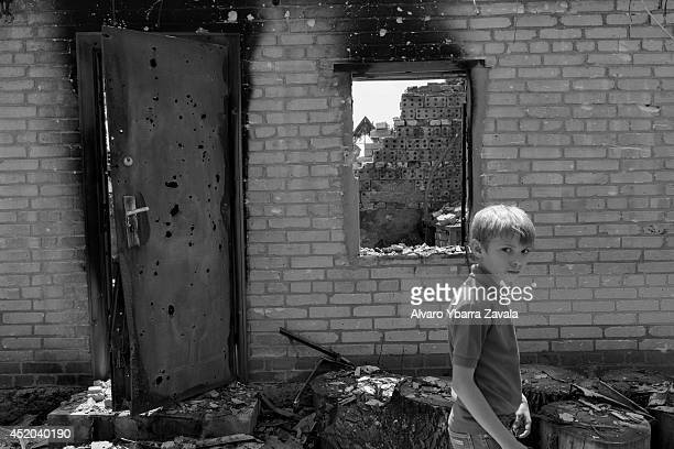Image has been converted to black and white A child walks through the remains of his house amongst the village ruins of Semyonovka on July 11 near...