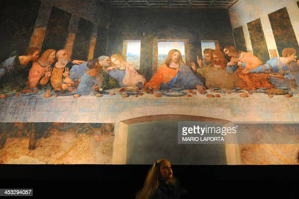 A child walks under a reproduction of 'The Last Supper' by artist Caravaggio as part of 'The Impossible Exhibition' at the San Domenico Maggiore...