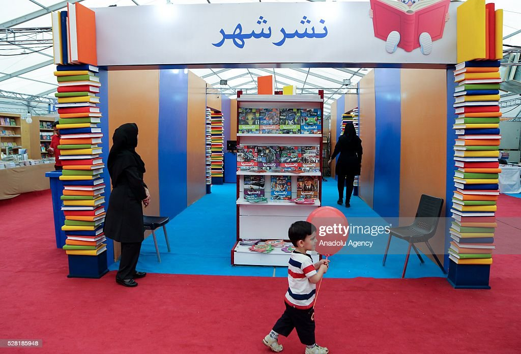 A child walks with his balloon as visitors inspect fair booths during 29th International Tehran Book Fair themed 'Tomorrow is late to read' at the Sun City Fair Complex in Tehran, Iran on May 4, 2016.