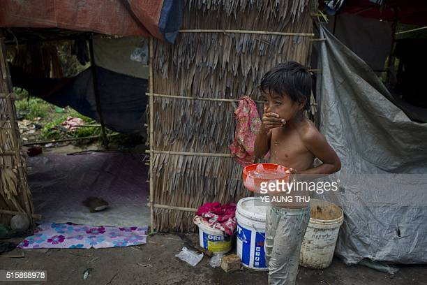A child washes his face beside makeshift huts for evicted residents in the outskirts of Yangon on March 16 2016 A novice administration led by Aung...