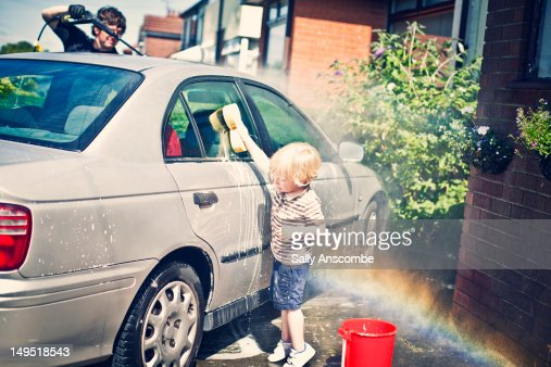 Child washing the car with daddy : Foto de stock