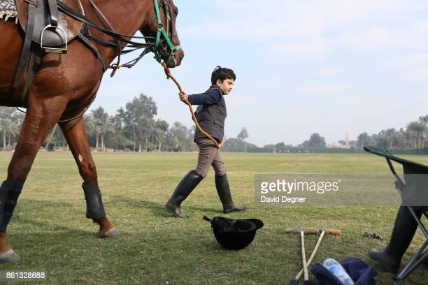 A child watches a horse as his father rides in a polo field near the Saqqara pyramids on December 06 2013 in Cairo Egypt There are a few polo teams...