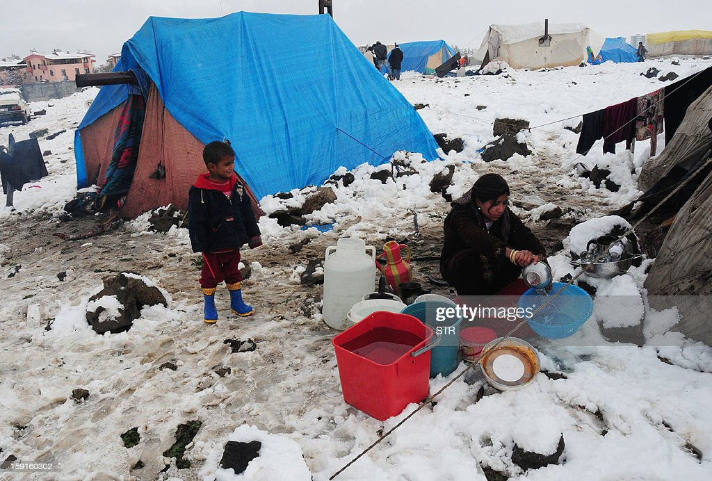 A child watches a woman washing a bassin at the Syrian refugee camp 5km from Diyarbakir, on the the way between Diyarbakir and Mardin, after snowfall, on January 9, 2013. The refugees faced further misery due to increasing shortages of supplies, low temperatures, and snowfall.