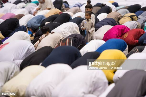 A child watches as men take part in prayers during the Eid in Excel event in association with the AlKhair Foundation at ExCeL London which is...