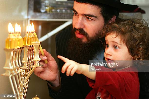 Child watching Father Lighting the Menorah