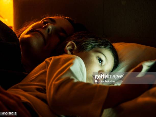 Child watching mobile phone and mother sleeps
