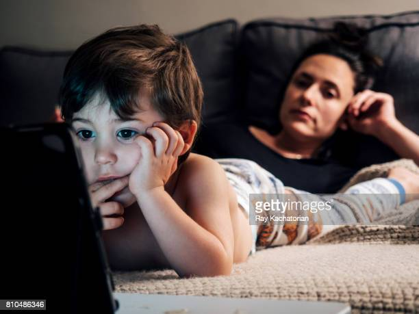Child watching tablet mother looking at child