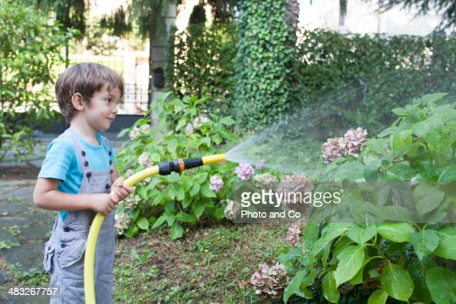 Child Watering Plants In Garden Stock Photo Getty Images