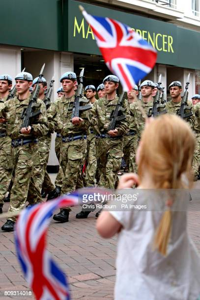 A child waves a flag as servicemen and women from 4 Regiment Army Air Corps parade through Ipswich Town Centre in Suffolk as they mark the unit's...