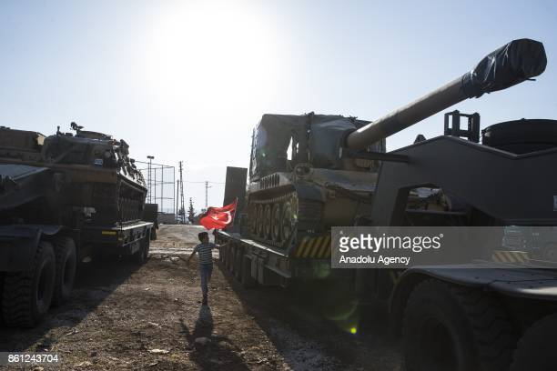 A child waves a Turkish flag as Turkish Army's armoured vehicles are deployed to the Reyhanli border due to the transition to Idlib deconflict zone...