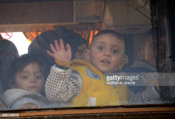TOPSHOT A child waves from the window of a bus as Syrians who were evacuated from Waer the last oppositionheld district of Homs arrive in the...