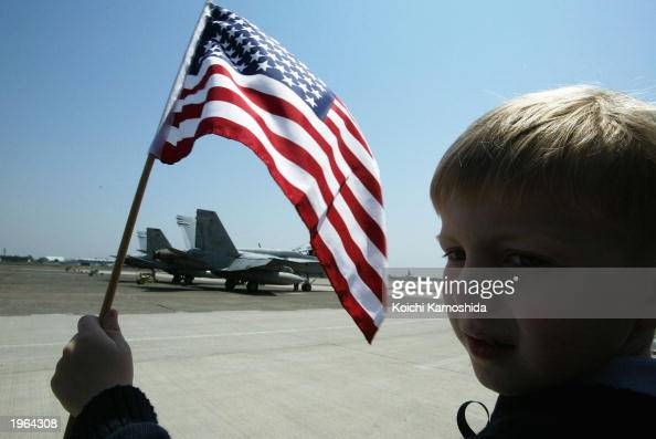 A child waves the stars and stripes as US personnel from Carrier Air Wing Five greet loved ones on May 1 2003 at Atsugi Naval Air facility in...