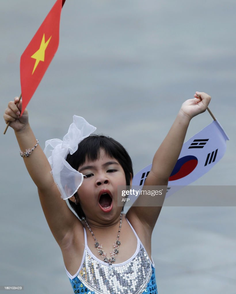 A child waves Vietnamese and South Korean flags prior to the arrival of South Korean president Park Geun-Hye at the presidential palace in Hanoi on September 9, 2013. The South Korean leader arrived to Hanoi late September 7, 2013 from the G20 meeting in Russia for a three-day official visit aimed at boosting bilateral ties. AFP PHOTO/POOL/KHAM