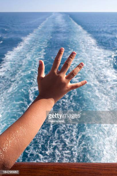 Child waving from the deck of a cruise ship.