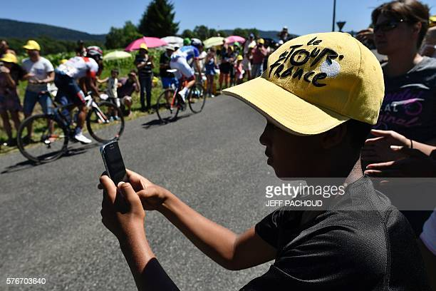 A child wearing a cap with the Tour de France logo takes pictures with a smartphone as cyclists ride past him during the 160 km fifteenth stage of...